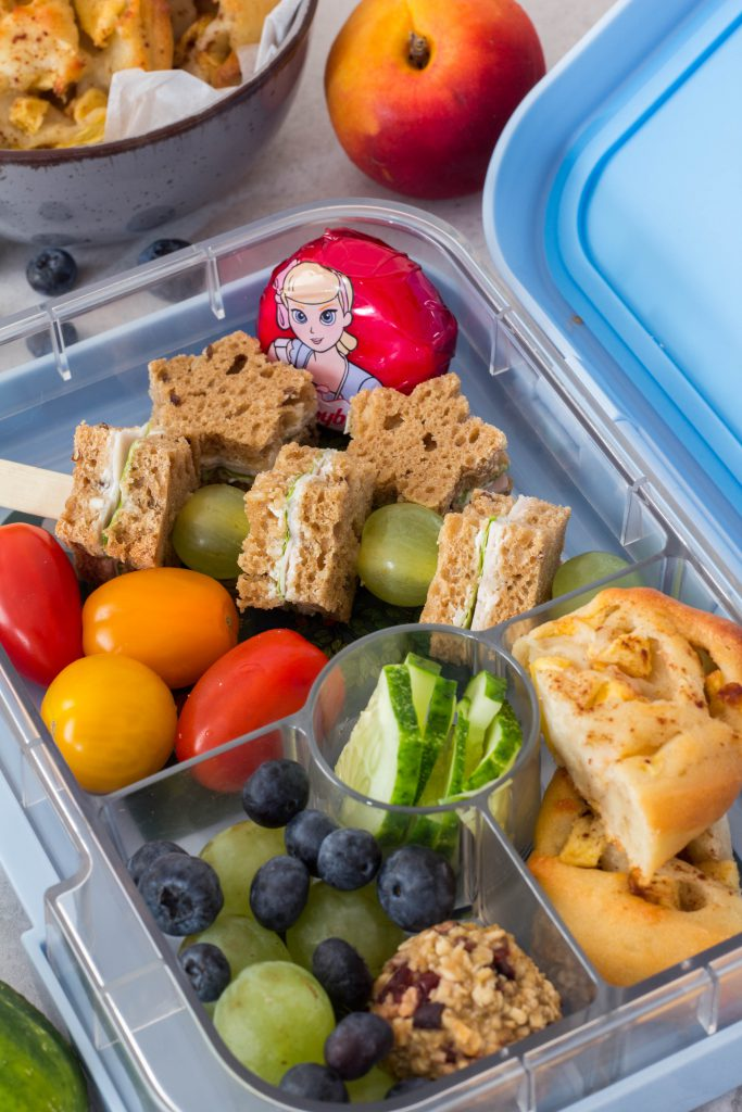 Gesunde Lunchbox für Kinder - Lecker gefüllte Brotdose mit Brotspießen, Trauben, Heidelbeeren, Tomaten, Käse und Apfel-Zimtschnecken. Lieblingszwei.de